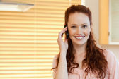 Woman with cellphone in the kitchen — Stock Photo