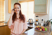 Woman with cellphone behind the kitchen counter — Stock Photo