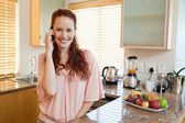 Smiling woman talking on the phone in the kitchen — Stock Photo