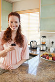 Woman in the kitchen with her cellphone — Stock Photo