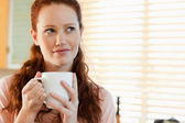 Woman with a cup in thoughts — Stock Photo