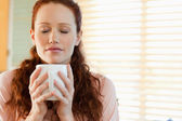 Woman enjoys the smell of her coffee — Stock Photo