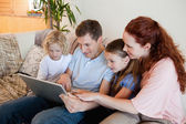 Family using notebook on the sofa — Stock Photo