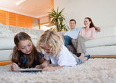 Children using tablet on the carpet — Stock Photo