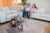 Brother and sister with laptop on the carpet — Stock Photo