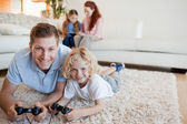 Father and son on the floor playing video games — Stock Photo