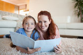 Mother and daughter looking at periodical — Stock Photo