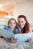 Mother and daughter with magazine on the the floor — Stock Photo