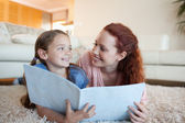 Mother and daughter with periodical on the floor — Stock Photo