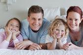 Famiglia sdraiata sul letto — Foto Stock