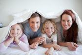 ベッドのカバーの下で幸せな家族 — ストック写真