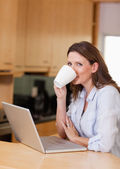 Woman taking a sip of coffee next to laptop — Stock Photo