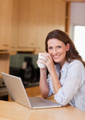 Woman with cup next to laptop — Stock Photo