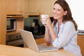 Woman with cup and notebook in the kitchen — Stock Photo