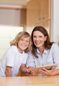 Woman and her son using tablet in the kitchen — Stock Photo