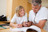 Boy doing homework with his father — Stock Photo