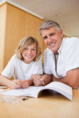 Boy getting help with homework from father — Stock Photo