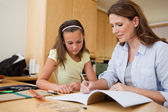 Mother helping daughter with her homework — Stock Photo