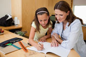 Girl doing homework with her mother — Stock Photo