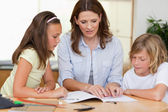 Woman helping children with homework — Stock Photo