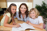 Mother helping her children with homework — Stock Photo