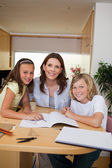 Siblings getting help with homework from mother — Stock Photo