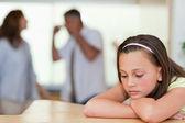 Smutna dziewczyna z rodzicami walki za nią — Zdjęcie stockowe