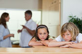 Sad looking siblings with fighting parents behind them — Stock Photo