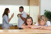 Hermanos mirando tristes con discutir los padres detrás de ellos — Foto de Stock