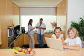Children with notebook in the kitchen and parents behind them — Stock Photo