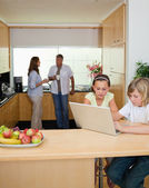 Siblings with notebook in the kitchen and parents behind them — Stock Photo