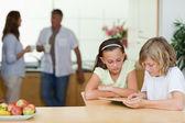 Niños que usan la tableta en la cocina con padres detrás de ellos — Foto de Stock