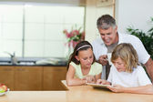Father with children and tablet in the kitchen — Stock Photo