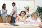 Parents talking with children doing homework in front of them — Stock Photo