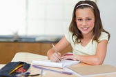 Smiling girl doing homework in the kitchen — Stock Photo