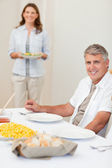 Man waiting for his wife to bring salad to the table — Stock Photo
