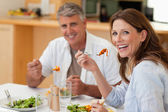 Laughing couple eating dinner — Photo