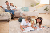 Siblings doing homework on the floor with parents behind them — Foto de Stock