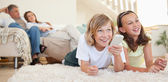 Siblings lying on the floor watching tv — Stockfoto