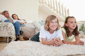 Frères et sœurs, couché sur le tapis devant la télé — Photo