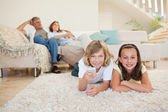 Siblings lying on the carpet watching tv — Stock Photo