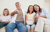 Family on the sofa watching tv — Stock Photo