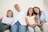 Laughing family sitting on the couch — Stock Photo
