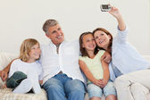 Mother taking a picture on the couch — Stock Photo