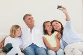 Mother taking a picture on the sofa — Stock Photo