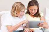 Siblings using tablet on sofa — Stock Photo