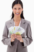 Smiling businesswoman with bank notes in her hands — Stock Photo