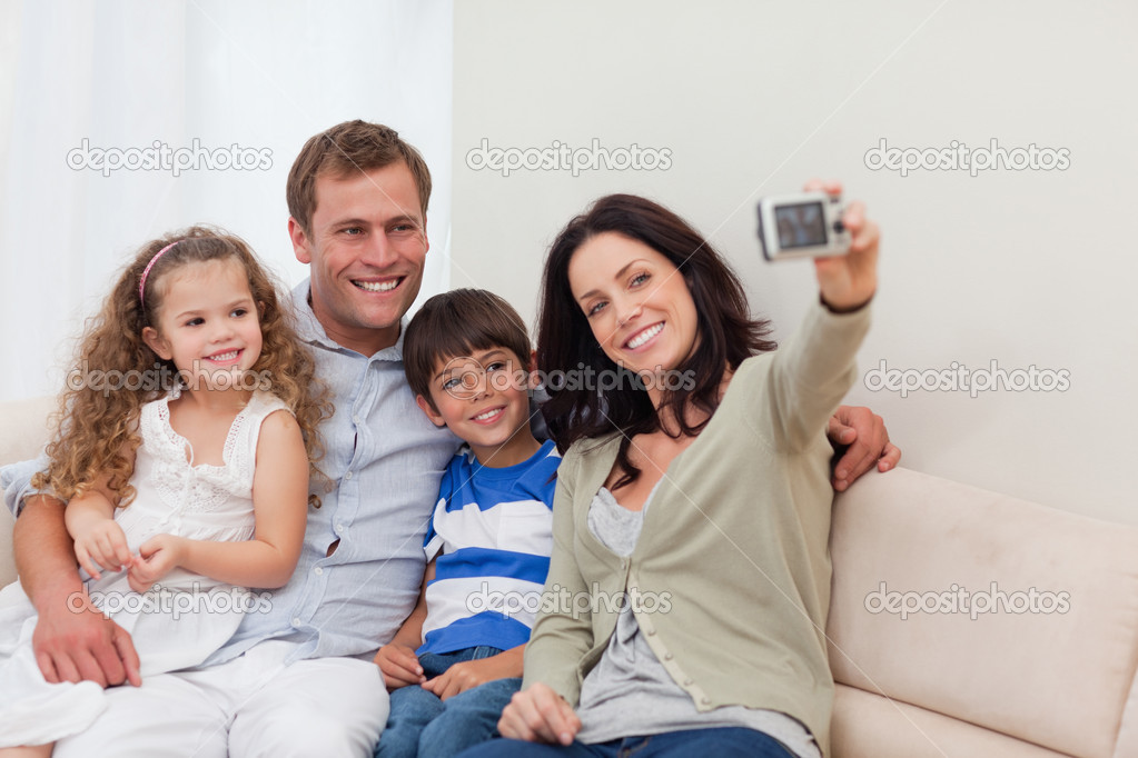 Young mother taking family photograph on the couch — Stock Photo #11210235