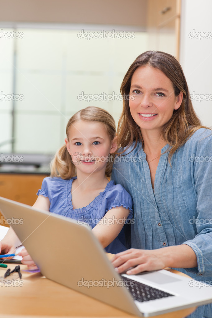 Portrait of a girl doing her homework while her mother is working with laptop in a kitchen — Stock Photo #11210576