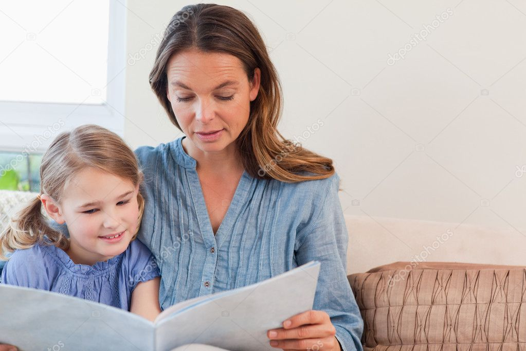 Mother reading a book to her daughter in a living room  Stock Photo #11210691
